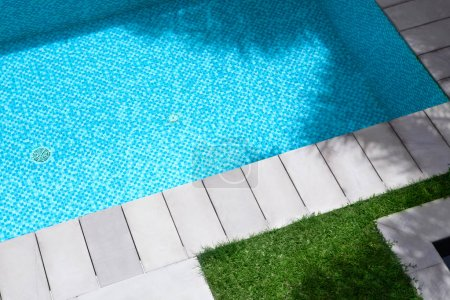 view of summer time swimming pool with grass and tiles around