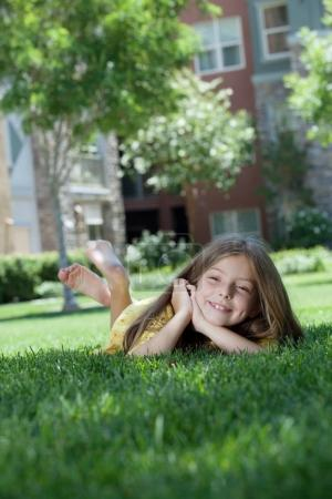 portrait of little girl laying on the grass in summer environment.