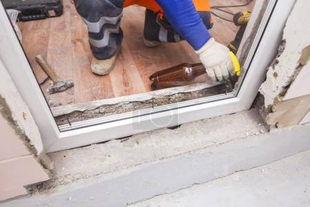 Photo for The worker installs plastic windows and doors - Royalty Free Image