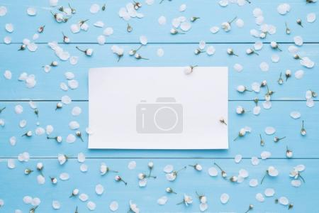 Foto de Hoja de papel vacía para el mensaje. Flores blancas sobre un fondo azul de la madera. Plantilla de diseño. Diseño plano, vista superior - Imagen libre de derechos