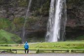 Tourist near a Seljalandsfoss waterfall in Iceland