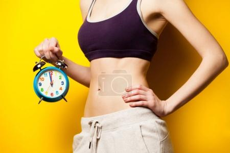 Photo of perfect slim female body with alarm clock in the hand o