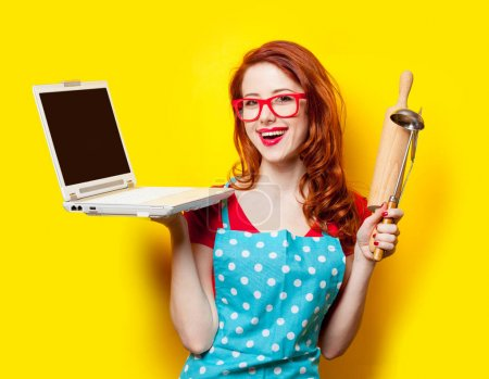 photo of beautiful young woman with cooking equipment and laptop