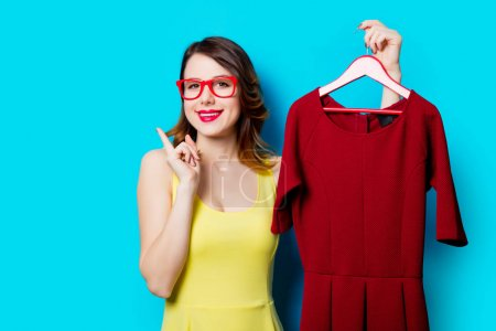young woman holding dress on hanger