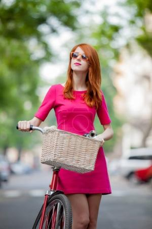 Portrait of redhead girl in sunglasses with bike in city