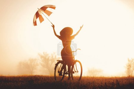 girl with umbrella riding on a bike