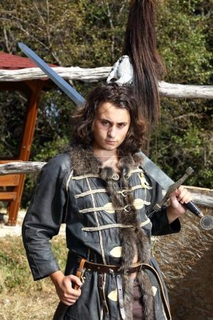 Photo pour Portrait de jeune guerrier avec épée - image libre de droit