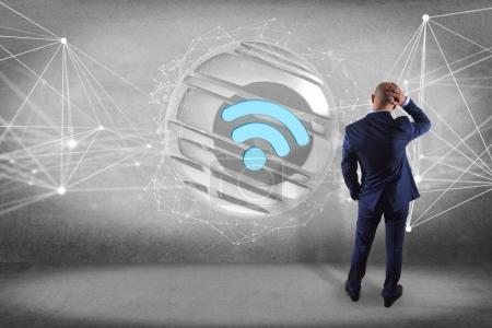 Businessman in front of a wall with wifi symbol