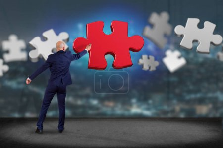 View of Businessman in front of wall with Puzzle pieces