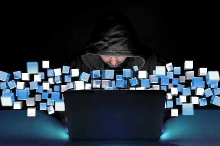 Hacker man in dark using computer to hack data and information system