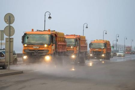 Trucks of city municipal services on cleaning of the embankment in the foggy spring afternoon
