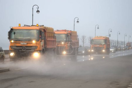 Cars of city municipal services wash Palace Embankment in the foggy March afternoon