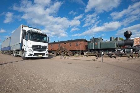 """Modern European truck with trailer """"Mercedes-Benz Actros"""" at an old train on a sunny June day. Kotka, Finland"""