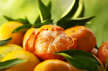 tangerines, peeled tangerine  on a green background