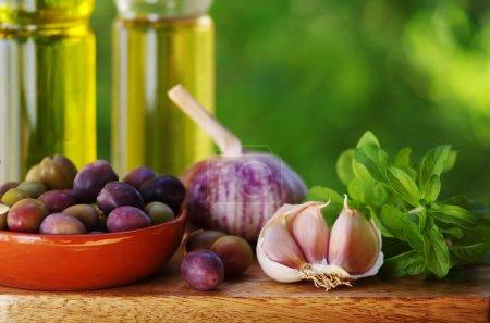 Photo pour Olives fruits, ail et herbes dans la table - image libre de droit