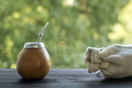Photo pour Yerba mate en matériau gourde avec sac en lin sur table en bois sur fond bokeh vert . - image libre de droit