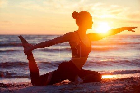 Photo pour Femme de fitness caucasienne pratiquant le yoga au coucher du soleil - image libre de droit