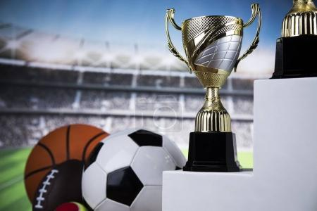 Cups of winners award on white podium, sport background