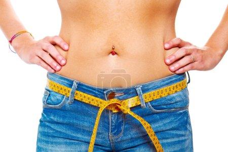 Photo pour Une jeune femme mince en jeans avec un mètre ruban adhésif après une alimentation réussie - image libre de droit