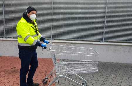 Photo for Coronavirus : man with medical mask and gloves are waiting with shopping cart out of the supermarket - Royalty Free Image