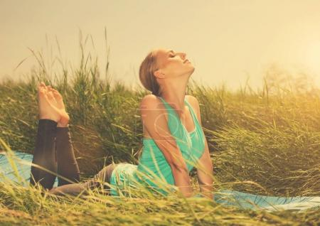 Photo for Pretty woman doing yoga exercises on the grass - Royalty Free Image