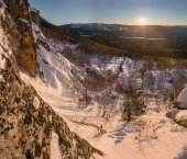 Beautiful Ural winter landscape with the setting sun over the mountain, the snow-covered woods and rocks