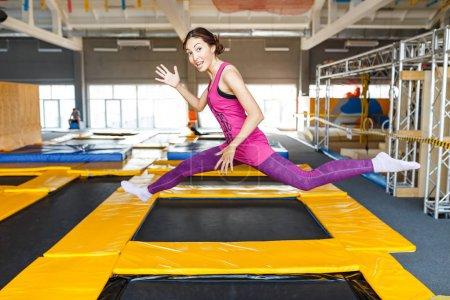 Photo pour Femme joyeuse et heureuse pratiquant et sautant sur des trampolines dans un centre sportif intérieur, un entraînement et un concept de divertissement moderne - image libre de droit