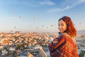Woman in traditional poncho clothes watching wonderful view of a colorful hot air balloons flying over the valley at Cappadocia, Turkey.