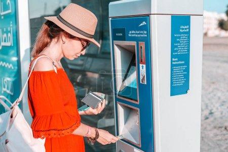 Photo pour 28 novembre 2019, Émirats arabes unis, Dubaï : Une touriste recharge sa carte de transport Nol au terminal Atm près de l'arrêt de bus - image libre de droit