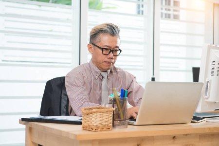 senior asian businessman at work
