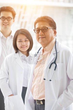 Photo pour Équipe de médecins asiatiques souriants en manteaux blancs - image libre de droit