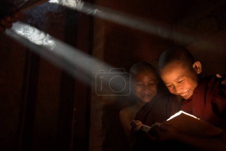 Photo for Monks reading in monastry in sunlight rays - Royalty Free Image