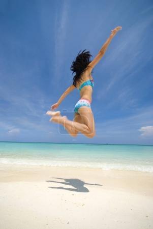 asian girl jumping in joy on a beach