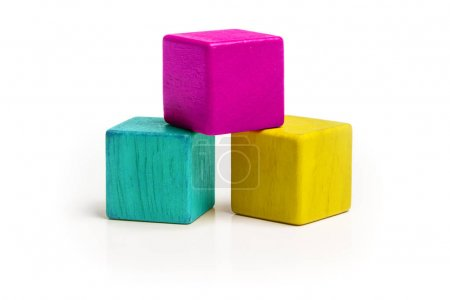 Photo for Toy Cube Blocks, CMYK Color Isolated over White Background, Three Kids Wood Toys, Cyan Magenta Yellow colors - Royalty Free Image