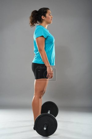 Photo for Young Fitness woman with heavy barbell doing dead-lift - Royalty Free Image