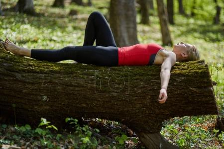 Young woman lying on tree trunk