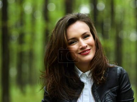Photo for Closeup portrait of smiling young woman in white t-shirt and black jacket in park - Royalty Free Image