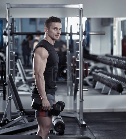 Young athletic man with dumbbells