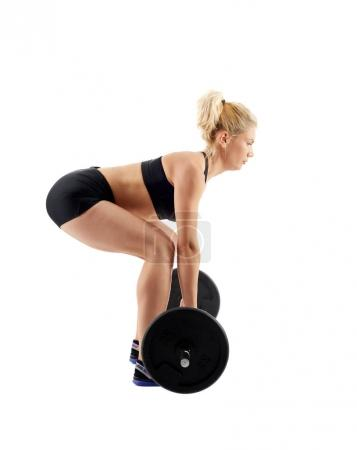 Woman doing deadlift with barbell