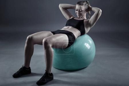 Photo pour Jeune femme faisant abdos croque avec une balle de gym - image libre de droit