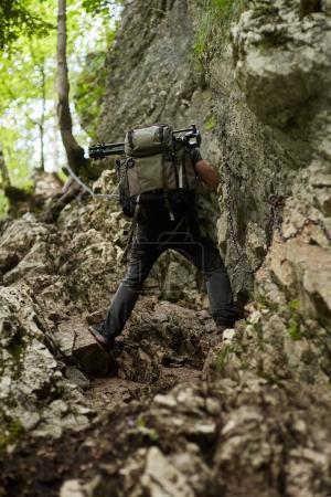 Photo pour Randonneur homme grimpant sur les chaînes de sécurité sur une piste difficile - image libre de droit