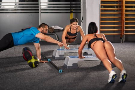 Photo for Fitness trainer and girls doing workout in the gym - Royalty Free Image