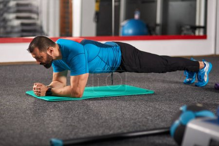 Fitness trainer doing planks in the gym