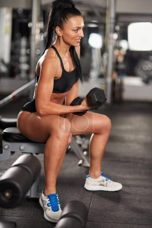 Athletic woman doing biceps curl