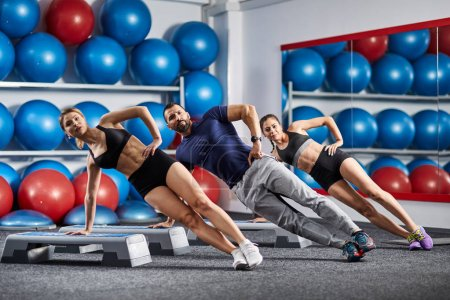 Side planking fitness trainer with girls