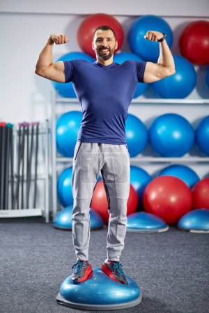 Fitness male trainer in the gym with equipment in background