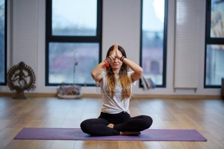 Young woman yoga practitioner or trainer indoor in various poses (asanas)