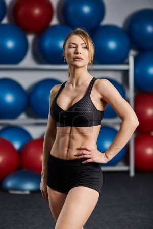 Young fit woman posing in sportswear in a gym
