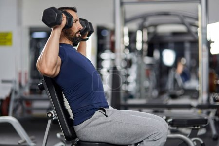 Man doing shoulder workout with dumbbells in the gym