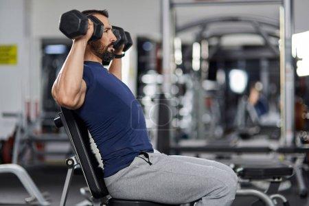 Photo pour Homme faisant épaule séance d'entraînement avec des haltères dans la salle de gym - image libre de droit